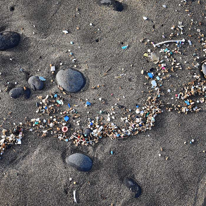 Small plastic parts and rocks in the sand