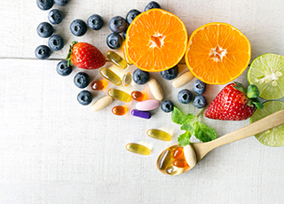 multivitamins on a wooden spoon with fresh fruit