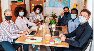 Group of people seated at conference room table wearing masks